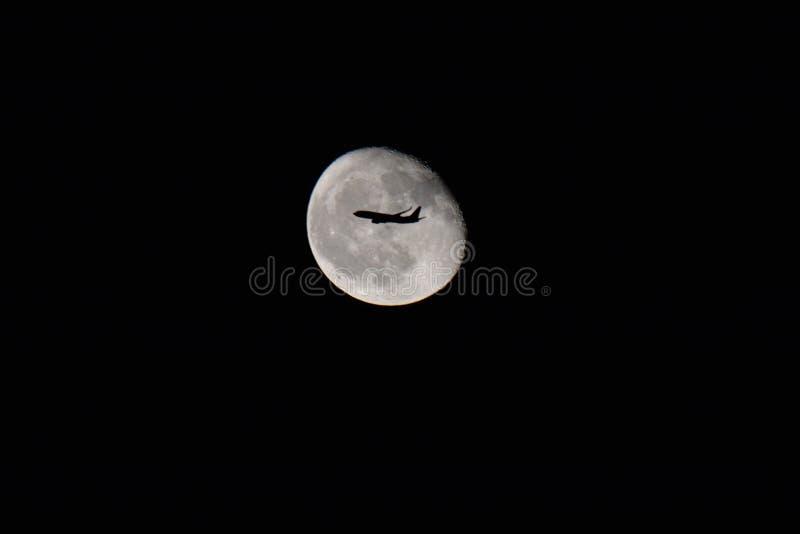 Silueta de un avión sobre la luna fotos de archivo libres de regalías