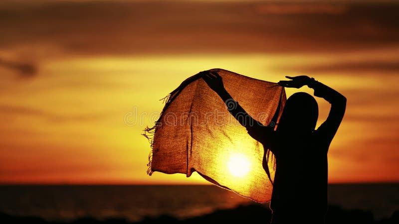 Silueta de un baile del hijab de la muchacha que lleva durante puesta del sol fotos de archivo