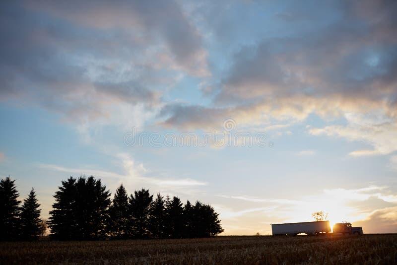 Silueta de un camión en el horizonte en la puesta del sol foto de archivo libre de regalías