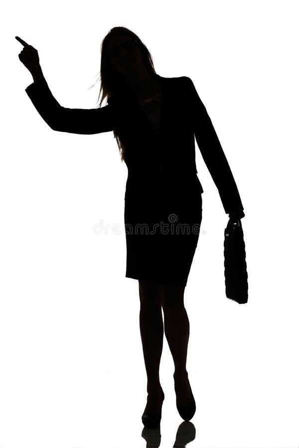 Silueta de un estudio ocupado del contraluz de la mujer de negocios imagenes de archivo