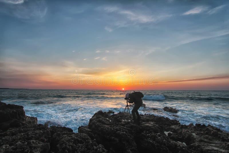 Silueta de un fotógrafo con una mochila y un trípode foto de archivo