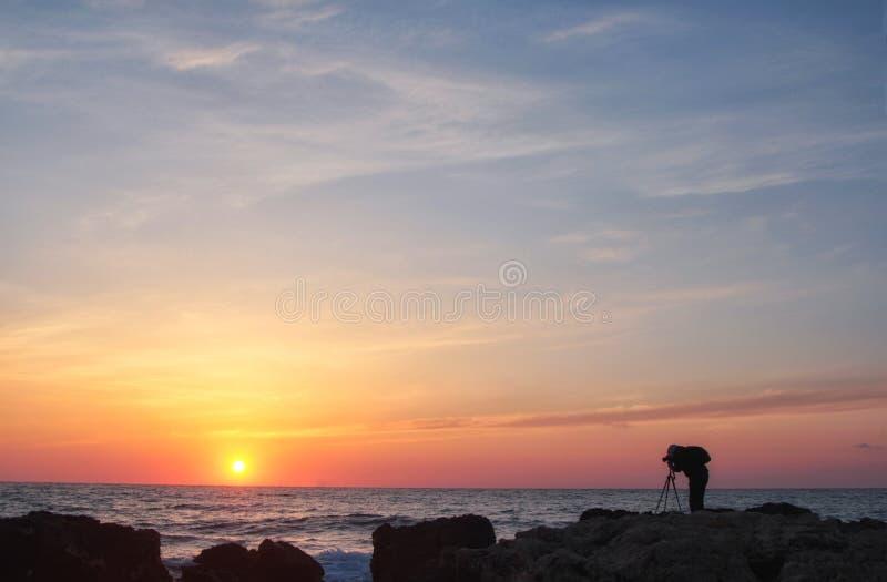 Silueta de un fotógrafo con una mochila y un trípode con una puesta del sol hermosa del mar fotos de archivo