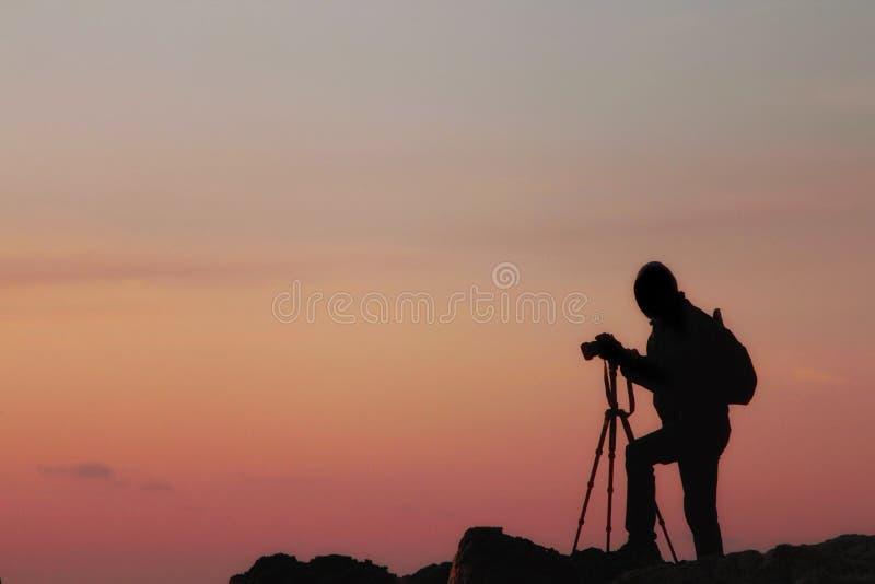 Silueta de un fotógrafo con una mochila y un trípode con una puesta del sol hermosa del mar fotografía de archivo libre de regalías