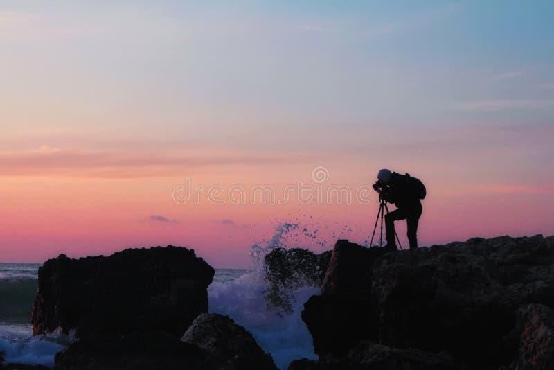 Silueta de un fotógrafo con una mochila y un trípode con una puesta del sol hermosa del mar imagenes de archivo