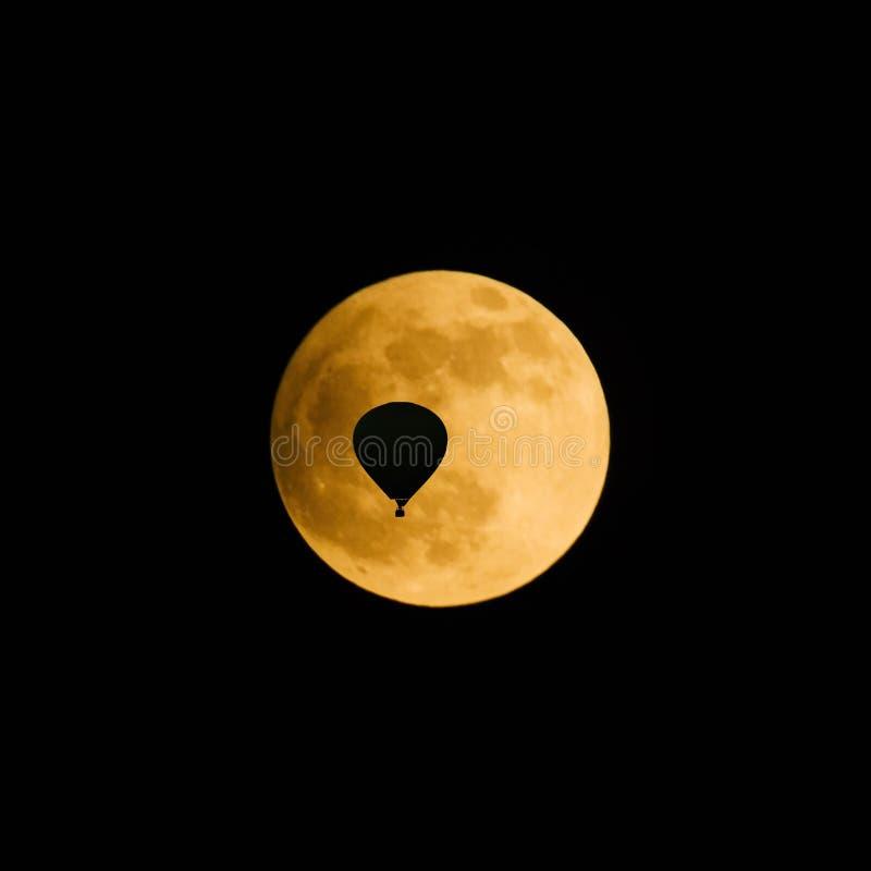 Silueta de un globo del aire caliente delante de la Luna Llena imagenes de archivo