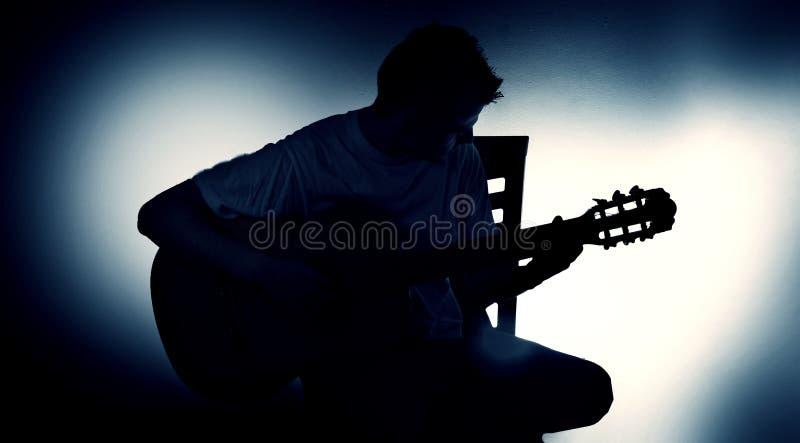 Silueta de un guitarrista con una guitarra acústica que se sienta en una silla, fondo negro fotografía de archivo