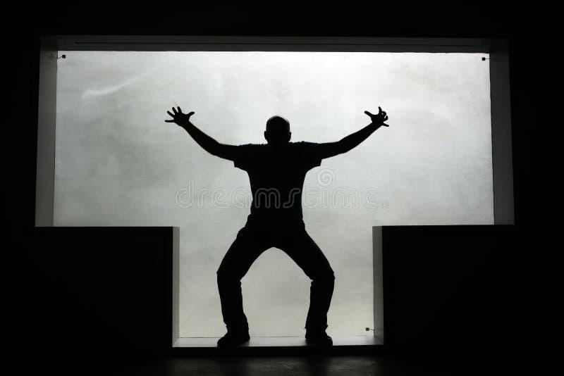 Silueta de un hombre con las piernas dobladas y las manos aumentadas en una ventana T-formada imagen de archivo libre de regalías