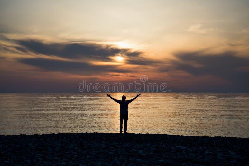 Silueta de un hombre con los brazos aumentados en la agua de mar en la puesta del sol imagen de archivo