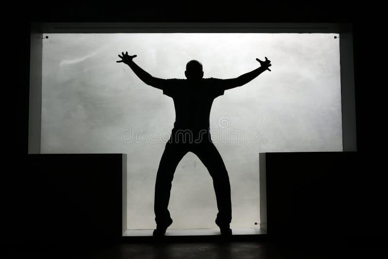 Silueta de un hombre de puntillas con las manos aumentadas en una ventana T-formada foto de archivo libre de regalías