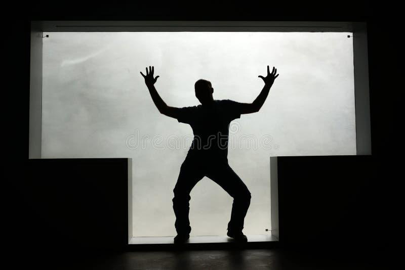 Silueta de un hombre del baile en una ventana T-formada foto de archivo libre de regalías