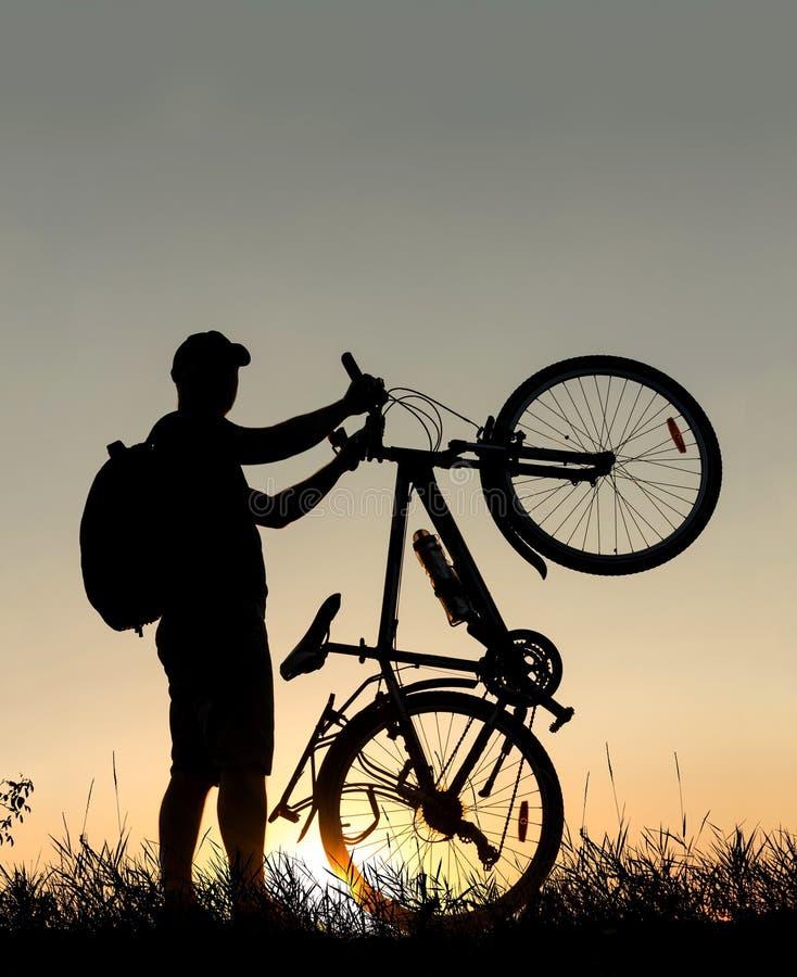 Silueta de un hombre del ciclista con una mochila en la puesta del sol con la bicicleta fotos de archivo