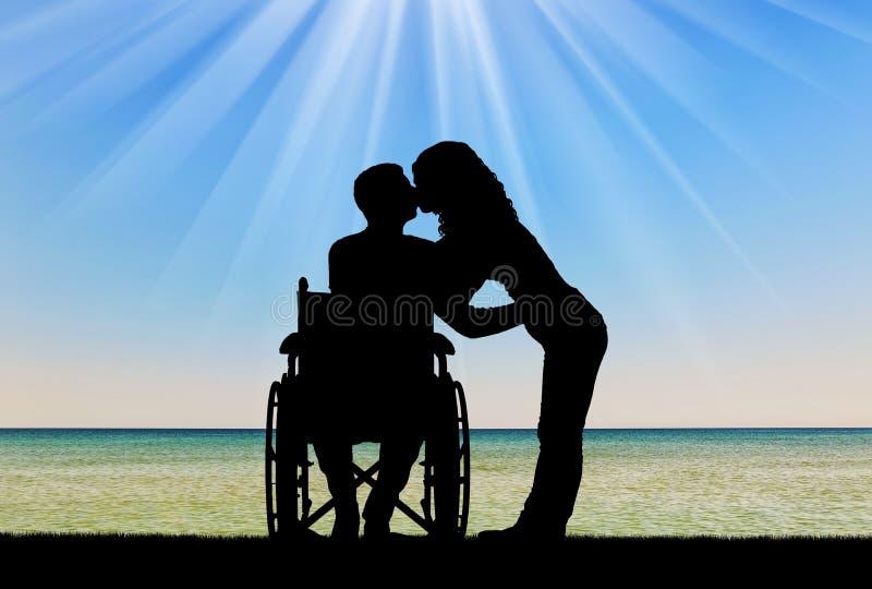 Silueta de un hombre discapacitado en una silla de ruedas y su esposa que se está besando por el mar fotografía de archivo