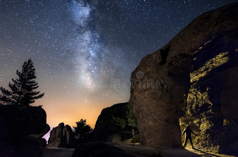 Silueta de un hombre en la noche que explora una cueva en la montaña con una antorcha debajo de un asombroso la vía láctea fotos de archivo