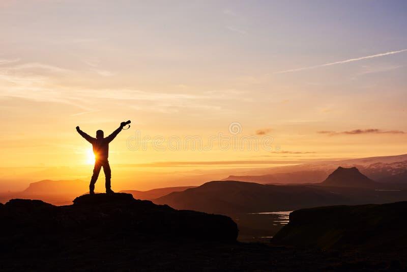 Silueta de un hombre en un top de la montaña Silueta de la persona en la roca Deporte y concepto activo de la vida fotografía de archivo