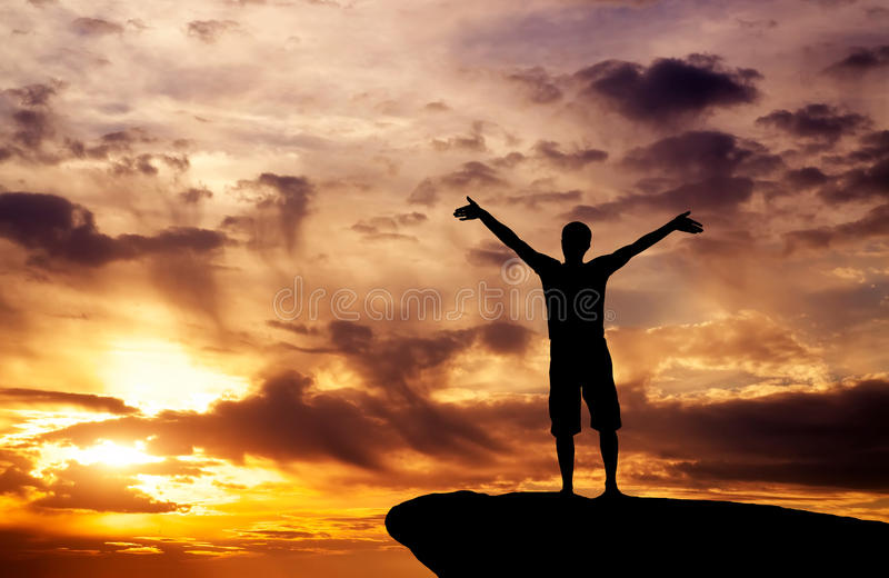 Silueta de un hombre en un top de la montaña imagenes de archivo
