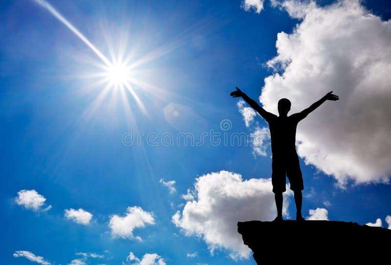 Silueta de un hombre en un top de la montaña Adoración a dios fotografía de archivo libre de regalías