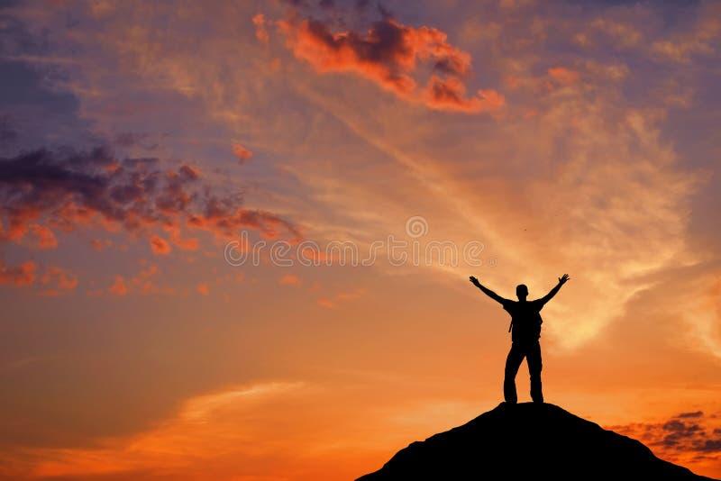Silueta de un hombre en un top de la montaña contra el cielo de la puesta del sol imágenes de archivo libres de regalías