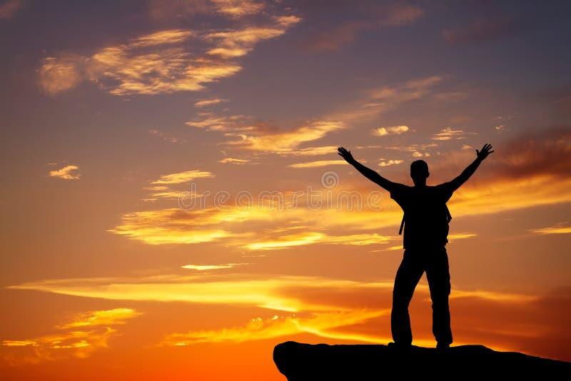 Silueta de un hombre en un top de la montaña en fondo ardiente fotografía de archivo libre de regalías