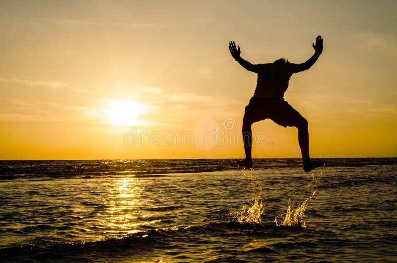 Silueta de un hombre en una posición de salto en el mar en el sunse imágenes de archivo libres de regalías