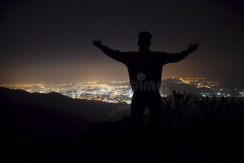 Silueta de un hombre joven con los brazos aumentados-para arriba, colocándose en el top de la montaña debajo del cielo nocturno c imagenes de archivo