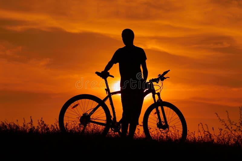 Silueta de un hombre joven con una bicicleta en la puesta del sol fotografía de archivo