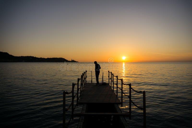 Silueta de un hombre que consigue listo para nadar en playa en puesta del sol imagen de archivo libre de regalías