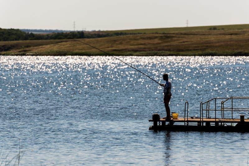 Silueta de un hombre que está pescando imagen de archivo