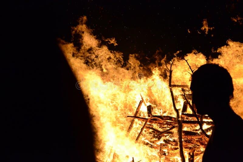 Silueta de un hombre que mira un fuego grande imagenes de archivo