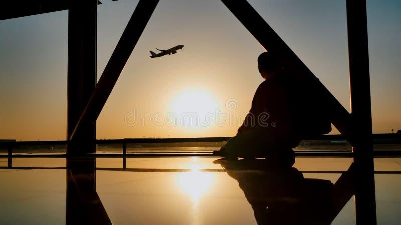 Silueta de un individuo turístico que mira el despegue del avión que se sienta en la ventana del aeropuerto en la puesta del sol  fotografía de archivo libre de regalías