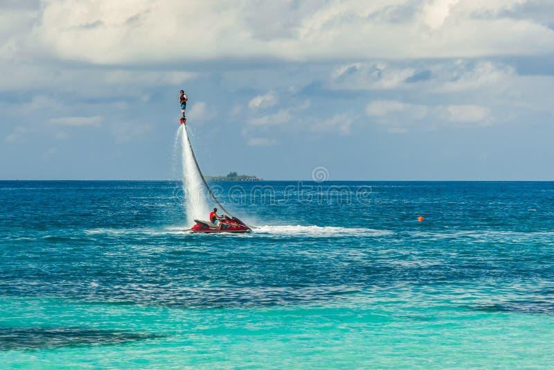 Silueta de un jinete del tablero de la mosca en el mar El jinete profesional hace los trucos en la laguna azul Equipo de deporte  fotos de archivo
