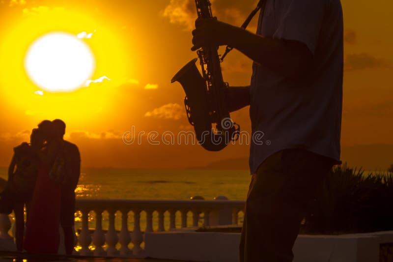 Silueta de un músico en la puesta del sol fotos de archivo libres de regalías
