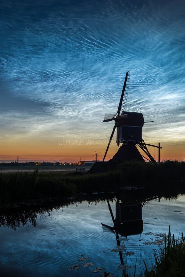 Silueta de un molino de viento holandés viejo contra un cielo con las nubes noctilucientes NLC alrededor de la medianoche imagen de archivo libre de regalías