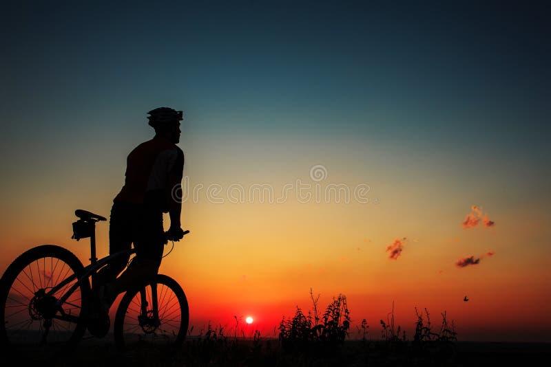 Silueta de un motorista y de una bicicleta en fondo del cielo imagen de archivo libre de regalías