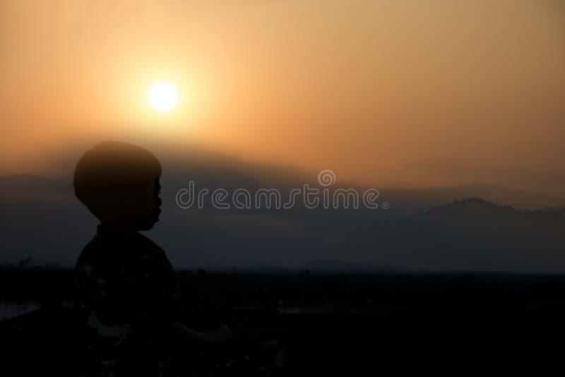 Silueta de un niño que se coloca a la vista del sol y de la montaña para relajarse foto de archivo libre de regalías