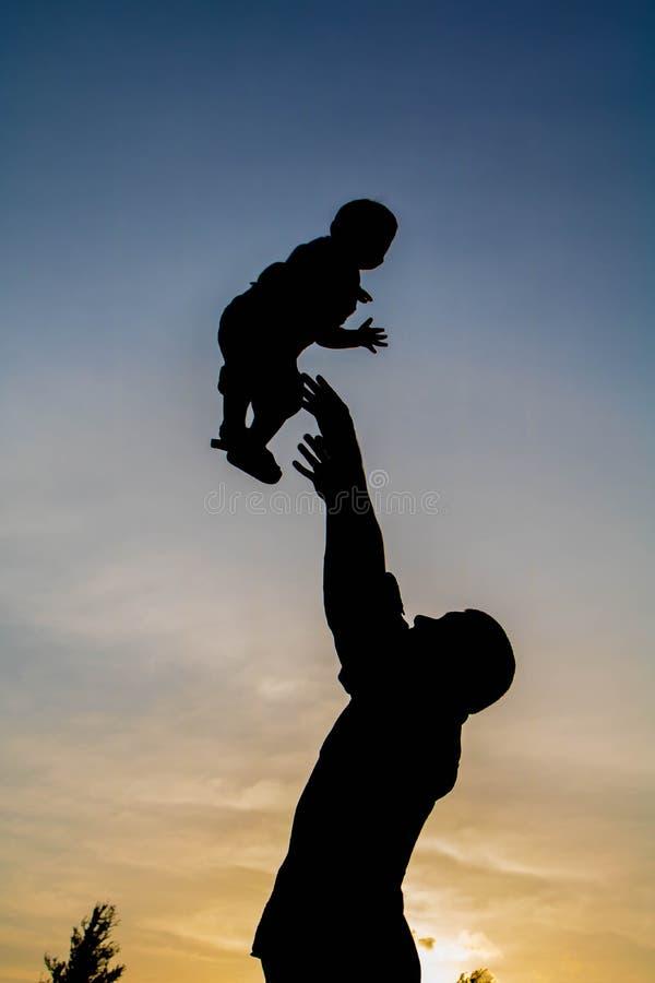 Silueta de un padre y de su bebé que juegan así como las nubes y el cielo en el fondo foto de archivo libre de regalías