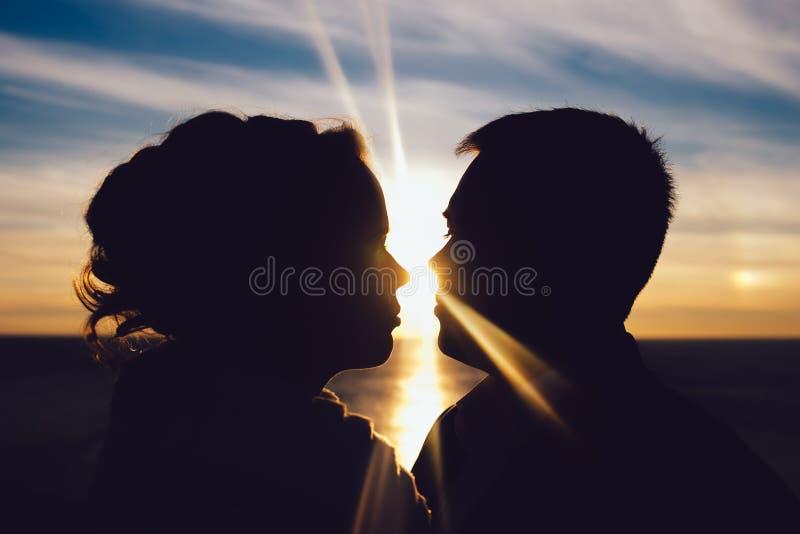 Silueta de un par cariñoso que se besa en la puesta del sol fotos de archivo