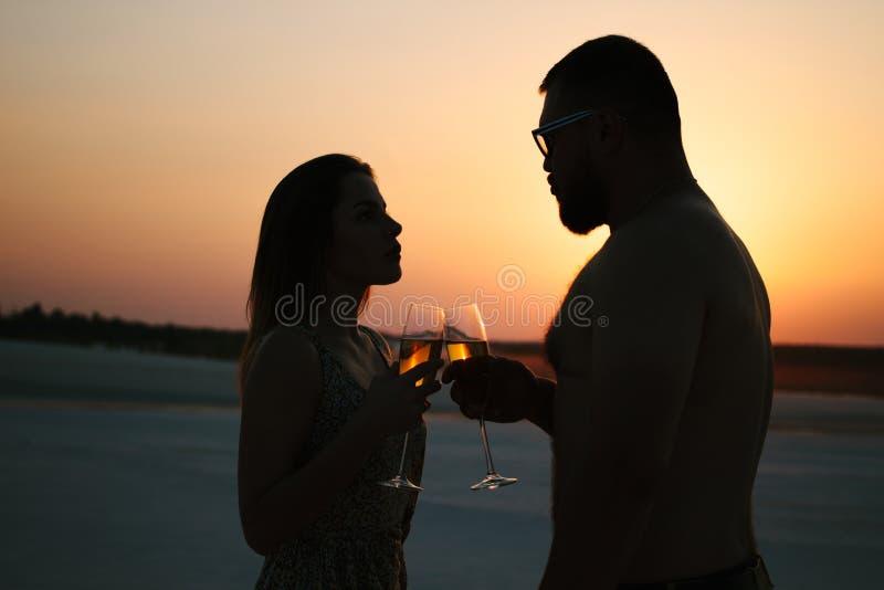 Silueta de un par con los vidrios en fondo de la puesta del sol, hombre y las copas de vino clanging de la mujer con champán en l imagen de archivo libre de regalías