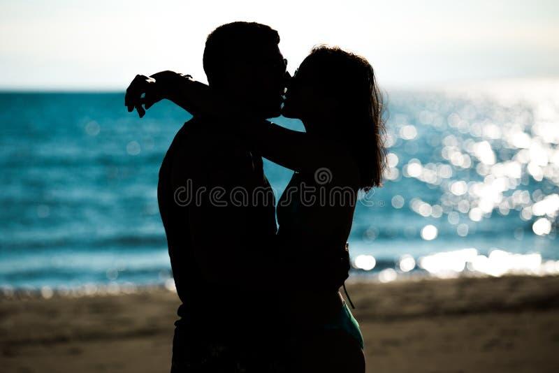 Silueta de un par en amor en la playa en la puesta del sol Historia de amor Hombre y una mujer en la playa foto de archivo libre de regalías