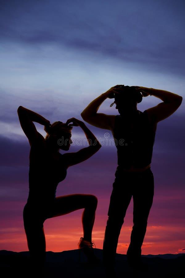 Silueta de un par en el vaquero de la puesta del sol que mira abajo foto de archivo libre de regalías