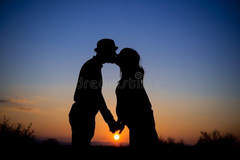 Silueta de un par en la puesta del sol, beso, maternidad fotos de archivo
