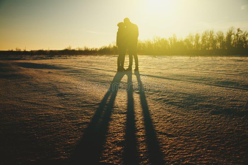 Silueta de un par joven que se besa en la gente de la puesta del sol imagenes de archivo