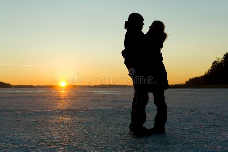 Silueta de un par que abraza en el hielo imagen de archivo libre de regalías