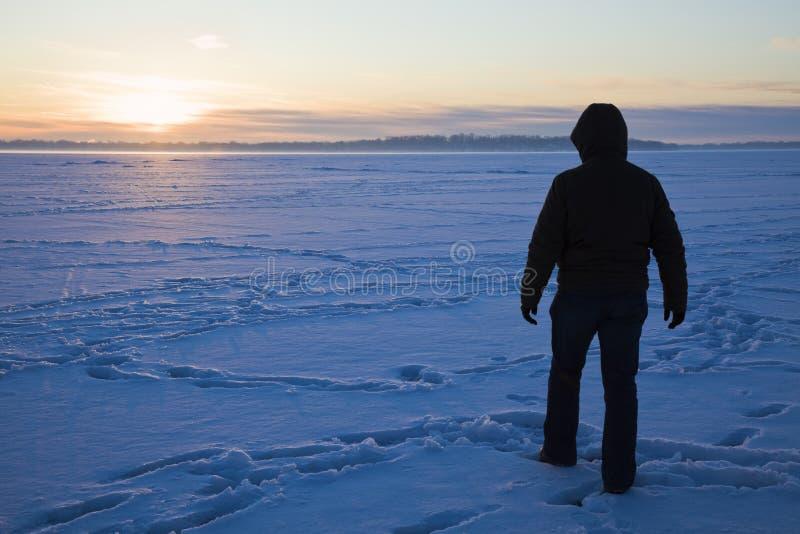 Silueta de un pescador que recorre en el lago fotografía de archivo