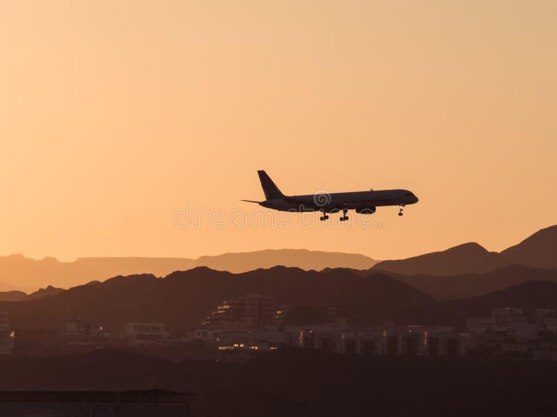 Silueta de un punto bajo que vuela plano sobre la ciudad y las montañas en la puesta del sol imagen de archivo