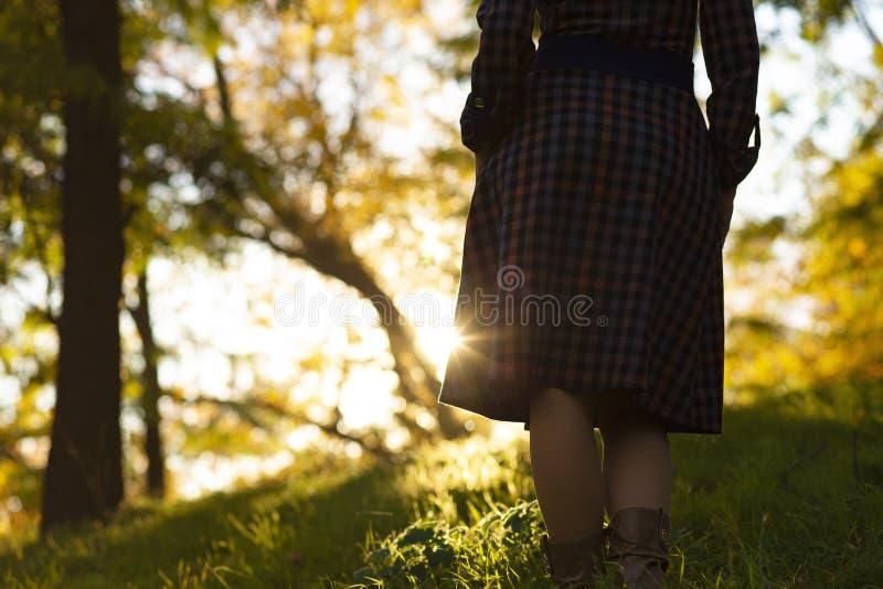Silueta de un risiong de la mujer joven para arriba en la colina en la puesta del sol, la figura muchacha en el paisaje del oto?o imágenes de archivo libres de regalías