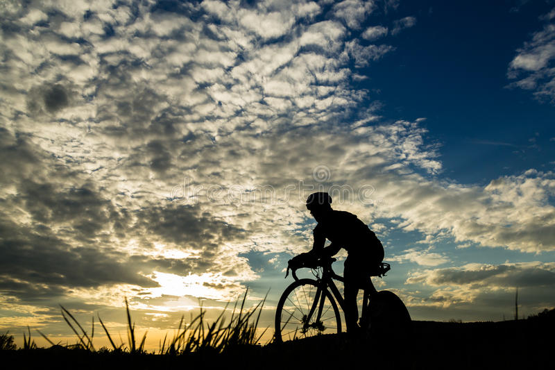 Silueta de un triathlete en puesta del sol imágenes de archivo libres de regalías