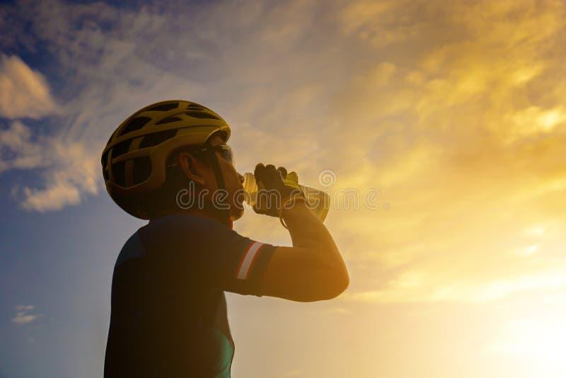 Silueta de un varón del ciclista que bebe un agua después de montar una Roa fotografía de archivo