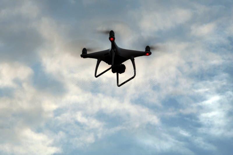 Silueta de un vehículo aéreo sin tripulación en las nubes El quadcopter vuela en el cielo Copie el espacio imagen de archivo libre de regalías