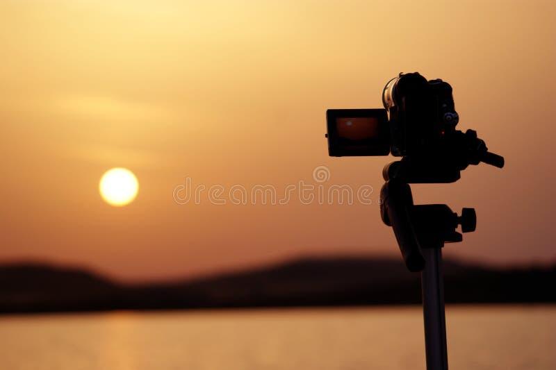 Silueta de una cámara que toma los vídeos de una puesta del sol foto de archivo