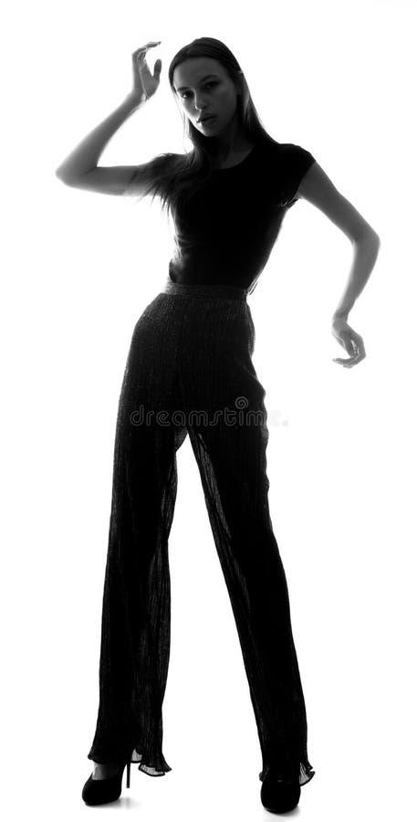 Silueta de una chica delgada con tacones altos sobre un fondo blanco imagenes de archivo